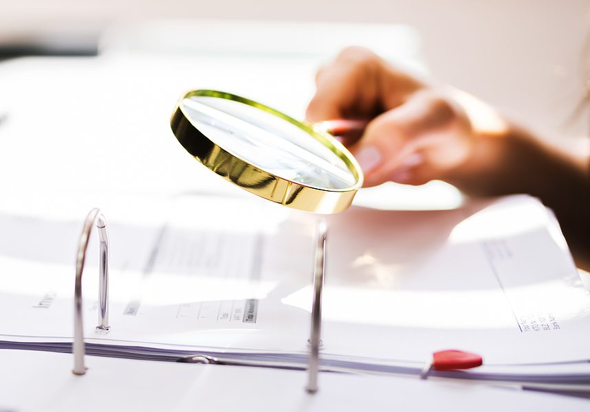 business auditor using magnifying glass for paperwork fraud investigation