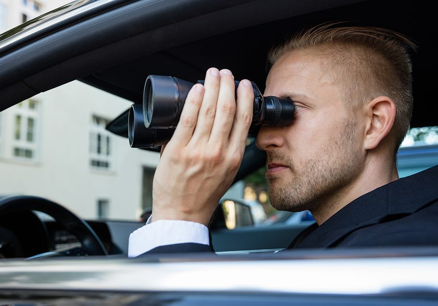 private detective inside the car looking through binocular