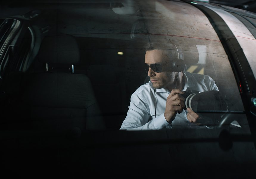 serious male private detective in headphones doing surveillance by camera with object glass from car